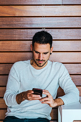 Portrait of young man sitting in a coffee shop using cell phone - p1166m2136818 by Cavan Images
