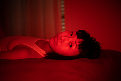 Asian woman in lingerie bathed in red light - p1321m2211719 by Gordon Spooner