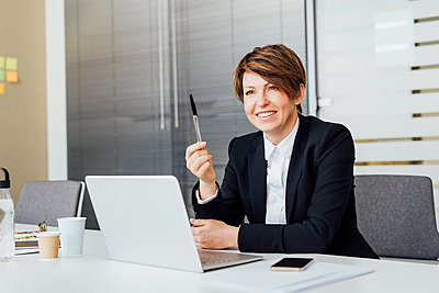 Smiling female entrepreneur holding pen in front of laptop at desk in office - p300m2275711 by Eugenio Marongiu