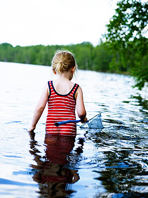 Scandinavia, Sweden, Girl (4-5) fishing in lake, rear view - p528m1075551f by Anna Kern