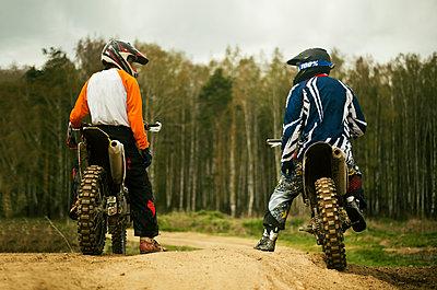 Caucasian men riding dirt bikes on road - p555m1306375 by Aleksander Rubtsov