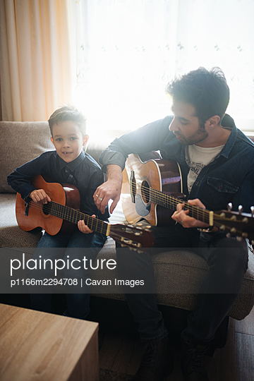 Daddy with son playing accoustic guitar. - p1166m2294708 by Cavan Images
