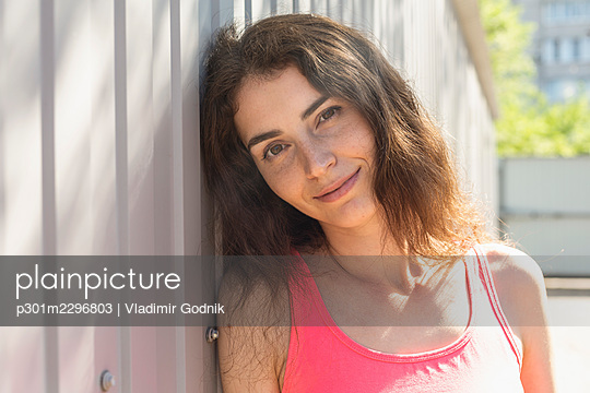 Portrait beautiful smiling young woman leaning against wall - p301m2296803 by Vladimir Godnik