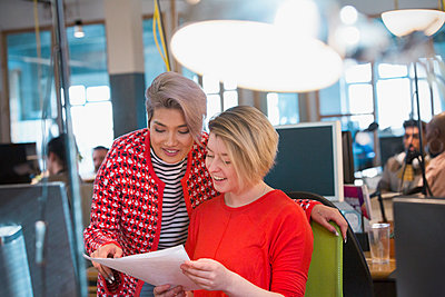 Creative businesswomen discussing paperwork in open plan office - p1023m2001545 by Chris Ryan
