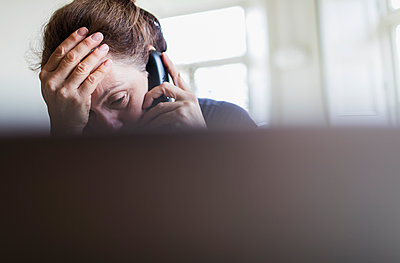 Tired woman talking on telephone at laptop - p1023m2201206 by Sam Edwards