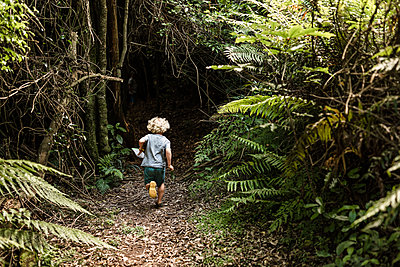 Young boy running into a lush forest - p1166m2130911 by Cavan Images