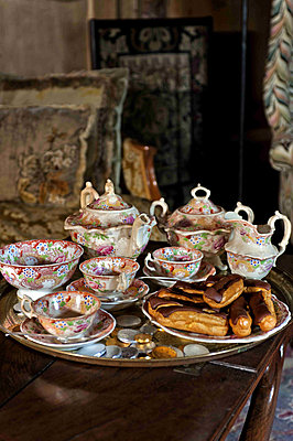 Teaset on tray with chocolate eclairs in Cheltenham country home - p349m790915 by Polly Eltes