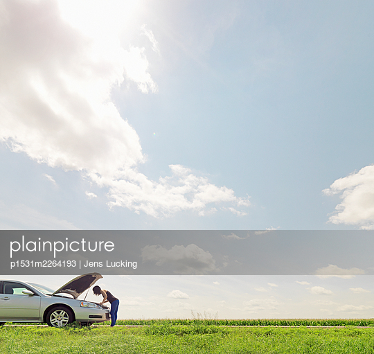 Woman checking under hood of broken-down car - p1531m2264193 by Jens Lucking