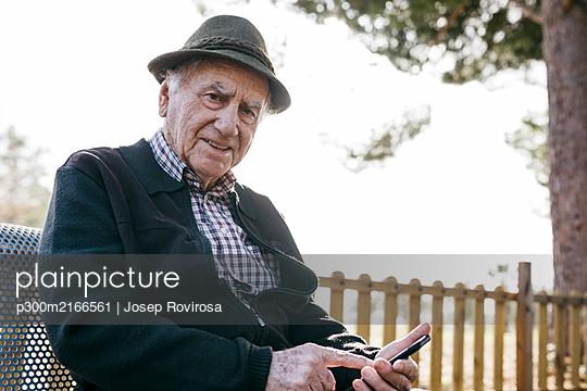 Spain, Barcelona. Retired senior man with his smartphone sitting on a park bench in winter - p300m2166561 von Josep Rovirosa