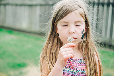 Young girl blowing a dandelion in the backyard - p1166m2208057 by Cavan Images