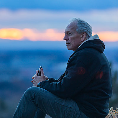 Seated man holding smart phone at sunset - p1427m2109958 by Steve Smith