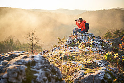 Woman on a hiking trip in the mountains sitting on rock looking through binoculars - p300m2083134 by Bartek Szewczyk