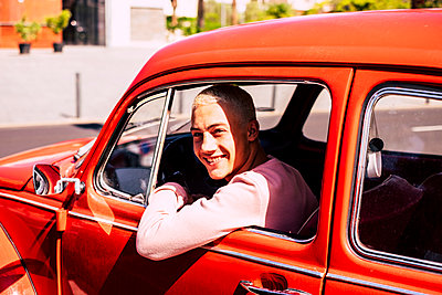Portrait of happy teenage boy sitting in vintage car looking out of window - p300m2203093 by Simona Pilolla