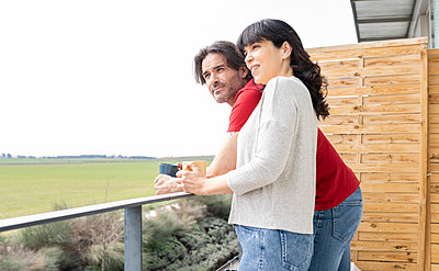 Mature couple looking away while having coffee in balcony - p300m2277268 by Jose Carlos Ichiro