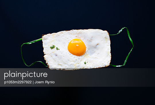 Fried egg sunny side up in the shape of a medical mask - p1053m2297922 by Joern Rynio