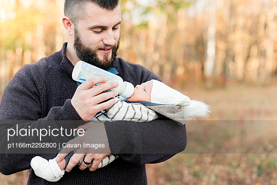 A father bottle feeding his newborn son during a walk - p1166m2292800 by Cavan Images