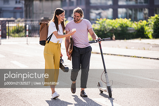 Young couple with electric scooter and smartphone walking on the street - p300m2132527 by Uwe Umstätter