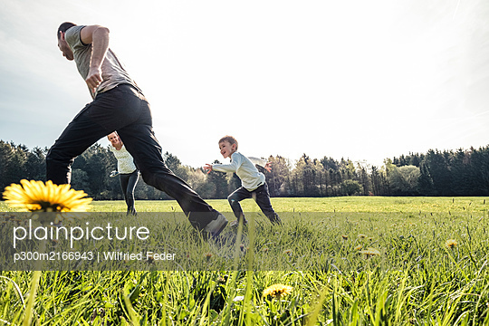 Family having fun together on a meadow in spring - p300m2166943 by Wilfried Feder