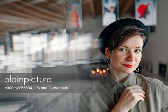 Fashionable woman wearing hat staring while standing at studio - p300m2256334 by Oxana Guryanova