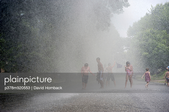 Children inside water spray - p378m920553 by David Hornback