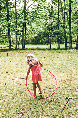 Little girl with Hula hoop - p1086m2149641 by Carrie Marie Burr