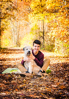 Teenage boy sitting with dog on leafy trail in the woods on fall day. - p1166m2147154 by Cavan Images