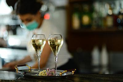 Female bartender wearing face mask prepare sparkling white wine - p1166m2201361 by Cavan Images