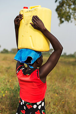 Africa, Uganda, Woman carrying water canister on her head - p1167m2283481 by Maria Schiffer