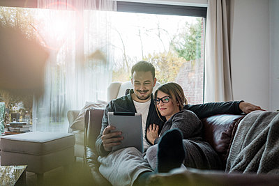 Smiling couple lying on couch at home sharing tablet - p300m1535104 by Robijn Page