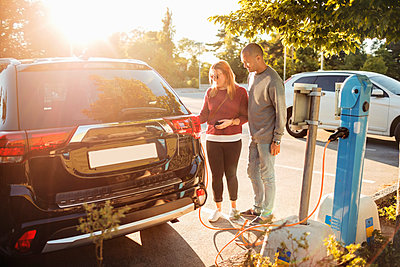 Mature couple charging electric car at station on sunny day - p426m1212725 by Maskot