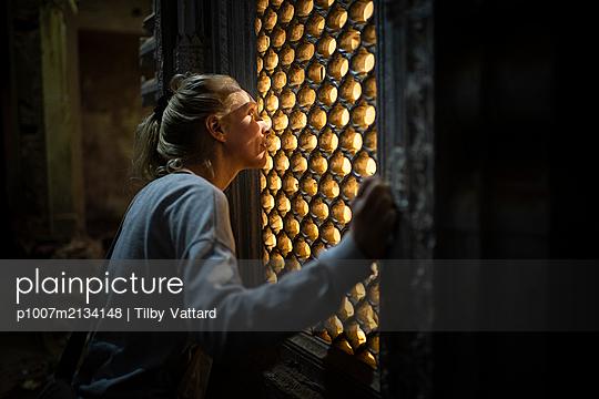Frau schaut durch ein Fenster - p1007m2134148 von Tilby Vattard