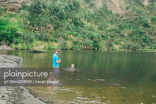 Family at a scenic river spot playing in the water - p1166m2208050 by Cavan Images