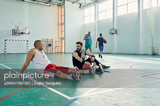 Basketball players during break, sitting on court - p300m1587301 von Zeljko Dangubic