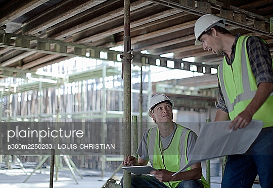 Male construction workers holding digital tablet while planning with coworker at construction site - p300m2250283 by LOUIS CHRISTIAN