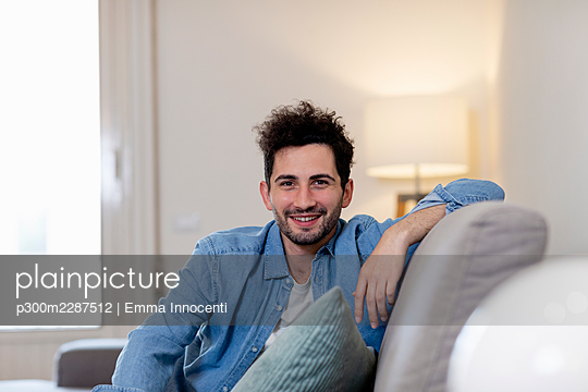 Portrait of young man with jeans shirt sitting on grey sofa smiling at camera; Florence, Italy - p300m2287512 von Emma Innocenti
