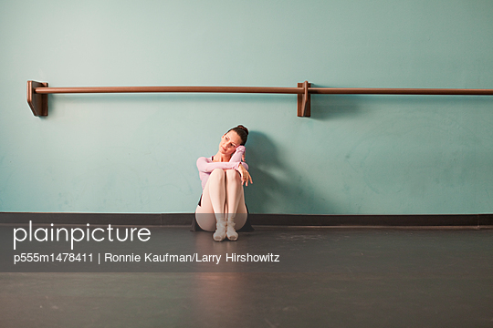 Caucasian ballet dancer sitting in studio