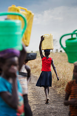 Africa, Uganda, Girl carrying water canister - p1167m2283447 by Maria Schiffer