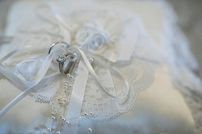 Close up still life wedding rings tied to white satin wedding pillow - p1192m1529792 by Hero Images