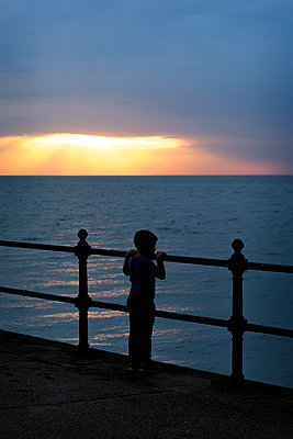 Young boy watching the sunset - p1228m2013351 by Benjamin Harte