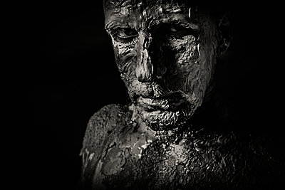 Man face with a beard covered with clay looking strongly at the camera  - p1619m2192735 by Laurent MOULAGER