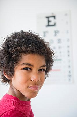Mixed race boy squinting near eye chart - p555m1421117 by JGI/Jamie Grill