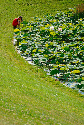 Young woman who takes photographs of water lilies - p6810061 by Sandrine Léon