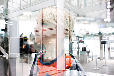 Blond haired boy gazing through window in airport, head and shoulders - p924m2138460 by Viara Mileva