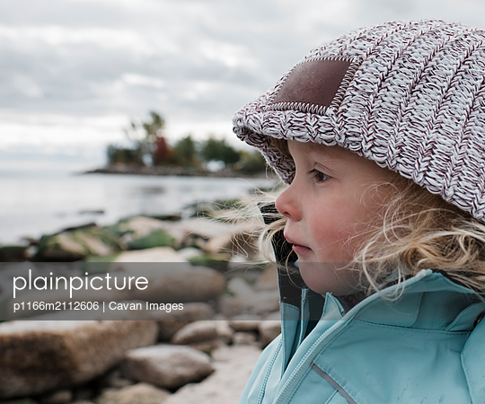 Side view of cute girl looking away while standing at rocky beach against cloudy sky - p1166m2112606 by Cavan Images