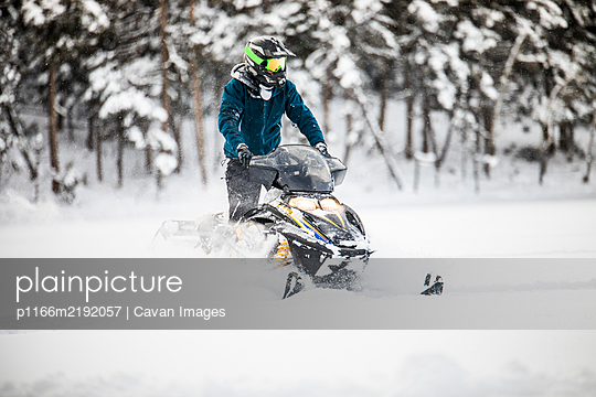 Front view of aggressive confident operator on snowmobile - p1166m2192057 by Cavan Images