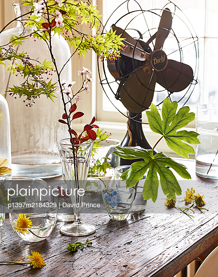 Table with vintage fan and flowers as decoration - p1397m2184329 by David Prince