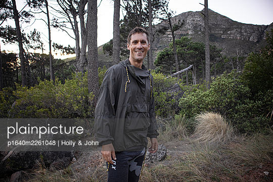 Hiker in a clearing, mountain range in the background - p1640m2261048 by Holly & John