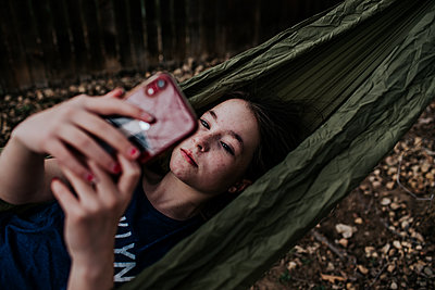 Teen girl laying in hammock taking photos on a phone - p1166m2201323 by Cavan Images
