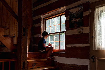 Boy sitting on steps of a log cabin cottage looking out through window - p1166m2207992 by Cavan Images