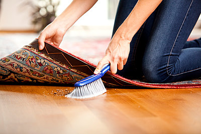 Woman sweeping under the carpet - p300m1059160f by Michelle Fraikin